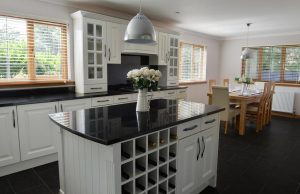 white kitchen units with black granite worktops